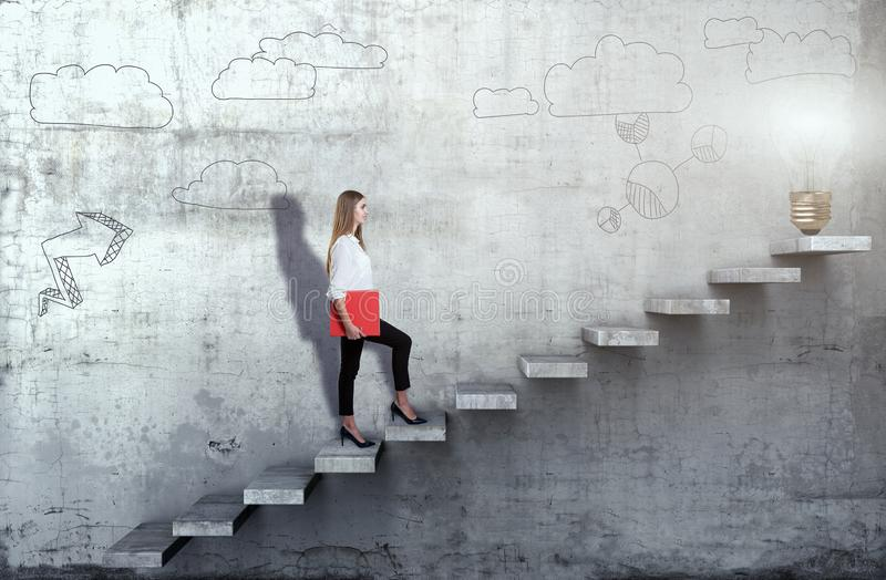Side view of young businesswoman climbing the stairs with idea lamp on concrete background. Successful business concept stock photos
