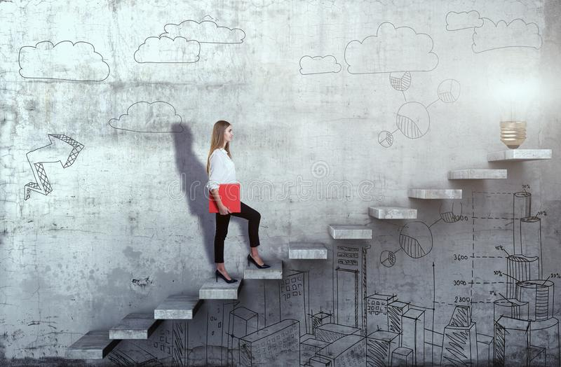 Side view of young businesswoman climbing the stairs with idea lamp on concrete background. Successful business concept stock image