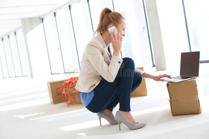 Side view of young businesswoman crouching while using mobile phone and laptop in new office.  stock image