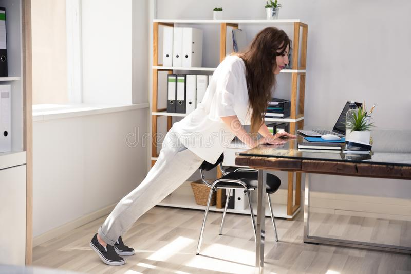 Young Businesswoman Doing Push Up. Side View Of A Young Businesswoman Doing Push Up At Workplace stock photos