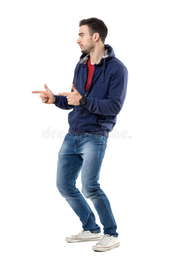 Side view of young casual guy pointing finger showing pistol hand gesture stock photography