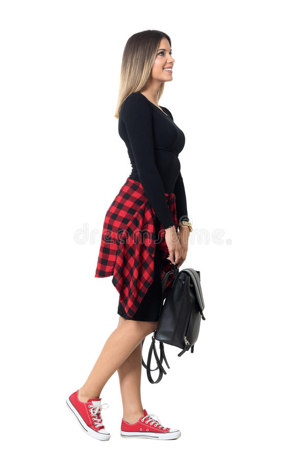 Side view of young casual style pretty student girl walking with black bag looking up. stock photography