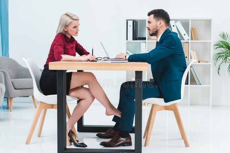 side view of young couple of business people looking at each other while working together and flirting under table stock photo