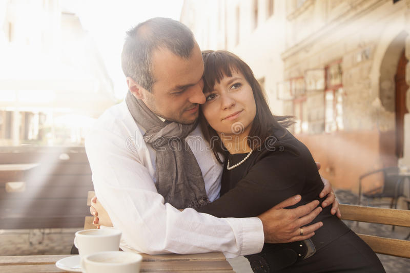 Side view of young couple enjoying coffee at outdoor restaurant royalty free stock photo