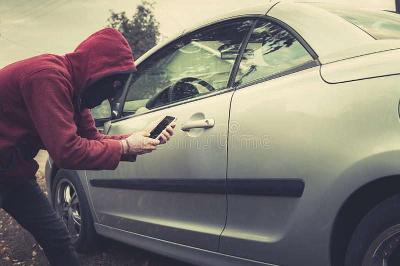 Side view of young criminal in black balaclava and hoodie holding smartphone and trying to interact with car by mobile royalty free stock image