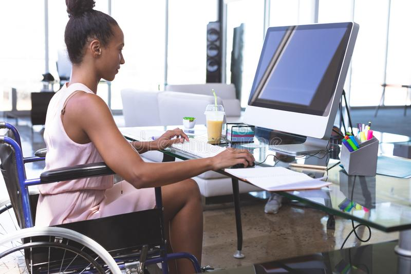 Disabled businesswoman working on computer at desk royalty free stock images