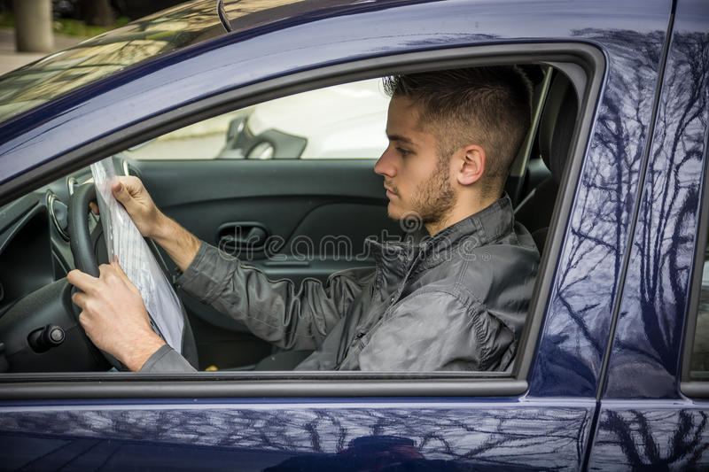 Side view of young driver reading document in car royalty free stock photography