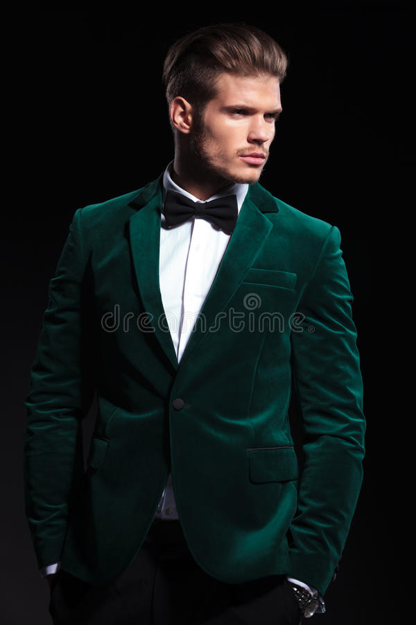 Side view of a young elegant man in green velvet suit. He looks away from the camera and stands with hands in pockets royalty free stock photography