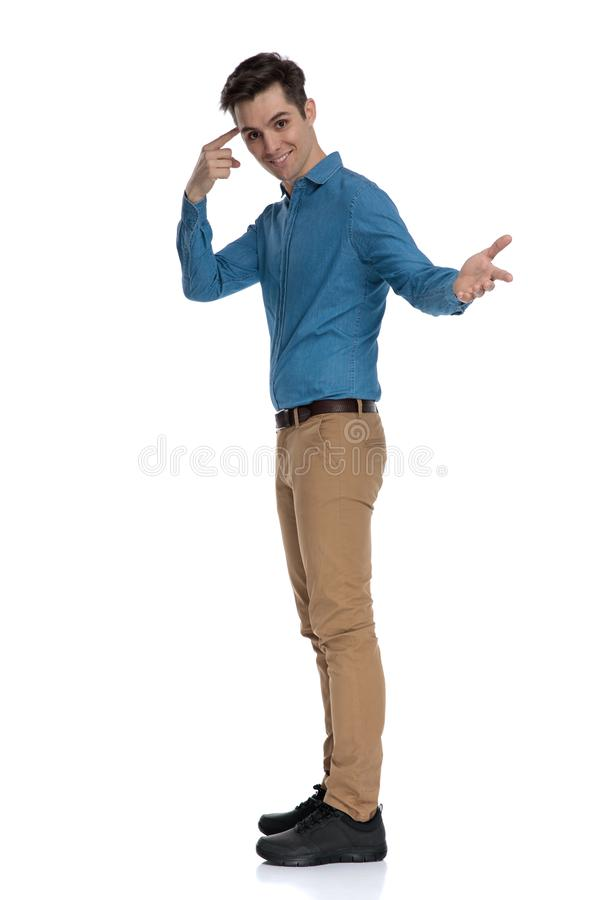 Side view of young fashion model pointing finger and inviting stock images