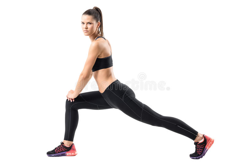 Side view of young female in sportswear doing forward lunge exercise. stock images