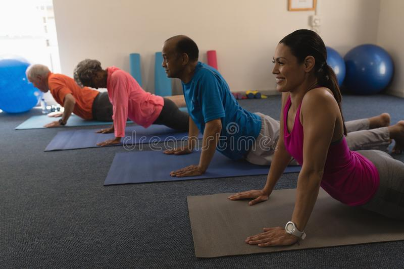 Side view of young female trainer exercising with senior people stock photography