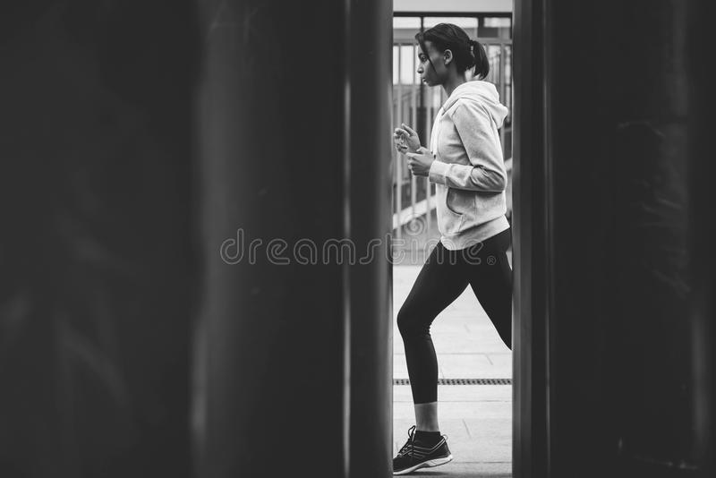 Side view of young fitness woman in sportswear jogging on stadium stock photos