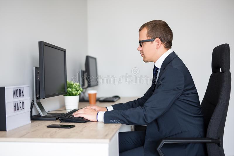 Side view of young handsome business man using computer in modern office royalty free stock photography
