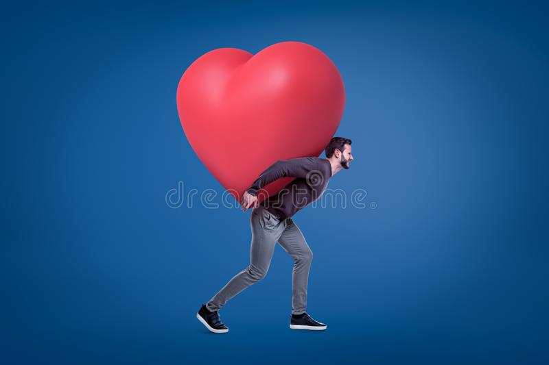 A side view of a young handsome man in a casual outfit carrying a huge red heart on his back. stock image