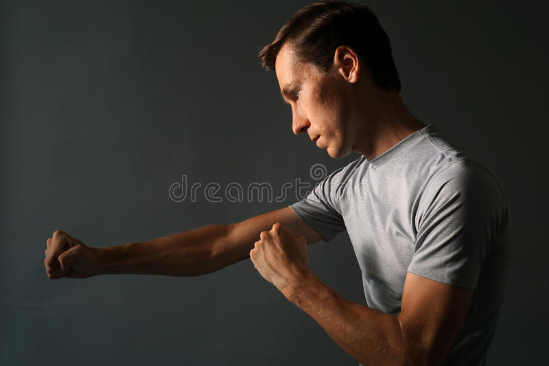 Side view of young handsome man making punches. Low key photography. stock photos