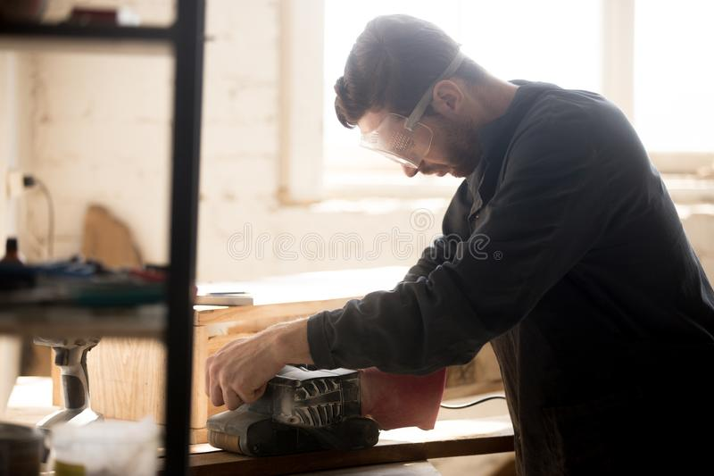 Serious skilled carpenter working using sander for grinding wood royalty free stock photos