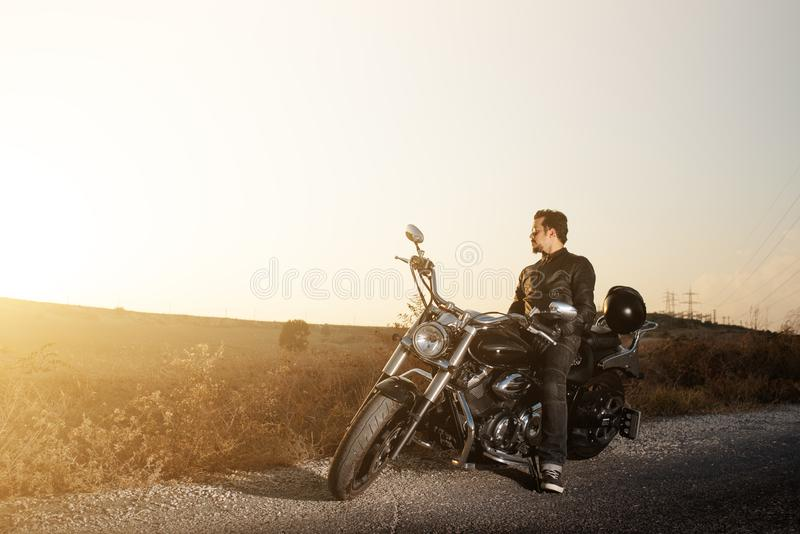 Side view of a young male  biker sitting on the side of the road against sunset while traveling by bike. royalty free stock image