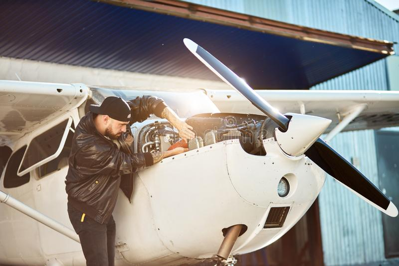 Side view of young male engineer inspecting small propeller airplane stock photo