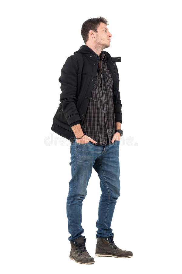 Side view of young man in autumn clothes with hands in pockets looking away stock photo