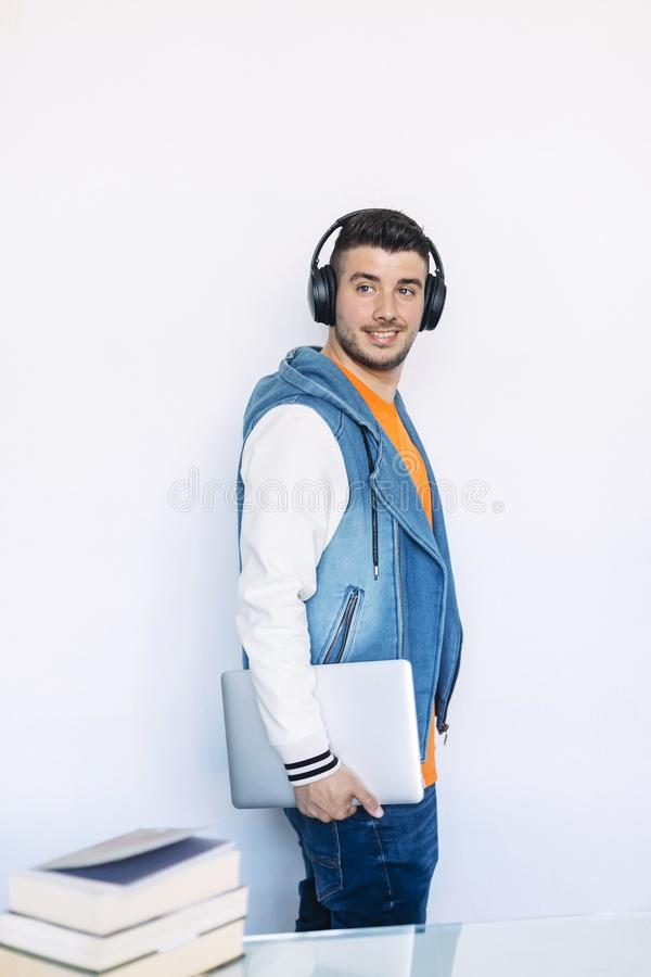 Side view of young man in casual clothes standing while looking away and carrying a tablet pc royalty free stock images