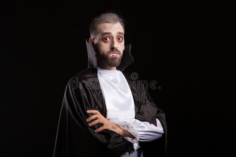 Side view of young man dressed up like a vampire looking curious into the camera royalty free stock photography