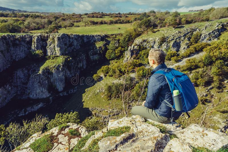 Side view young man hiker with backpack sitting on mountain`s top enjoying rocks landscape background. Travel lifestyle wanderlus. T adventure. Challange concept royalty free stock image