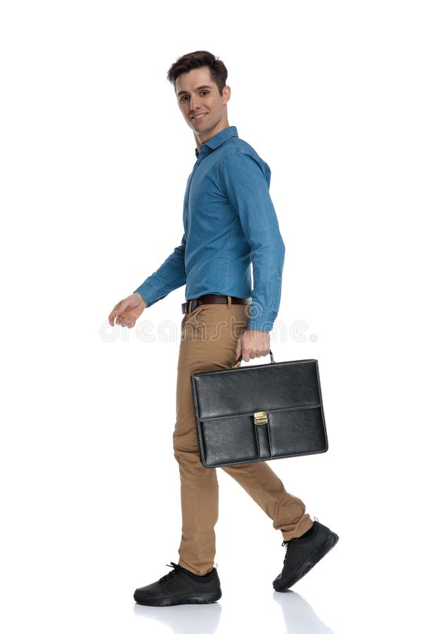Side view of young man smiling and holding suitcase stock photos
