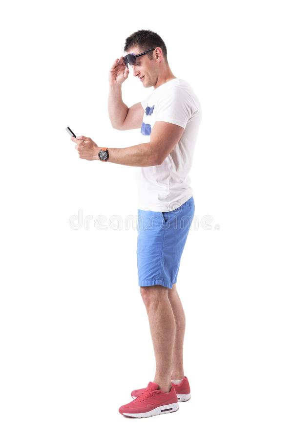 Side view of young man in summer clothes removing sunglasses to be able to see cellphone screen. Full body isolated on white background royalty free stock photography