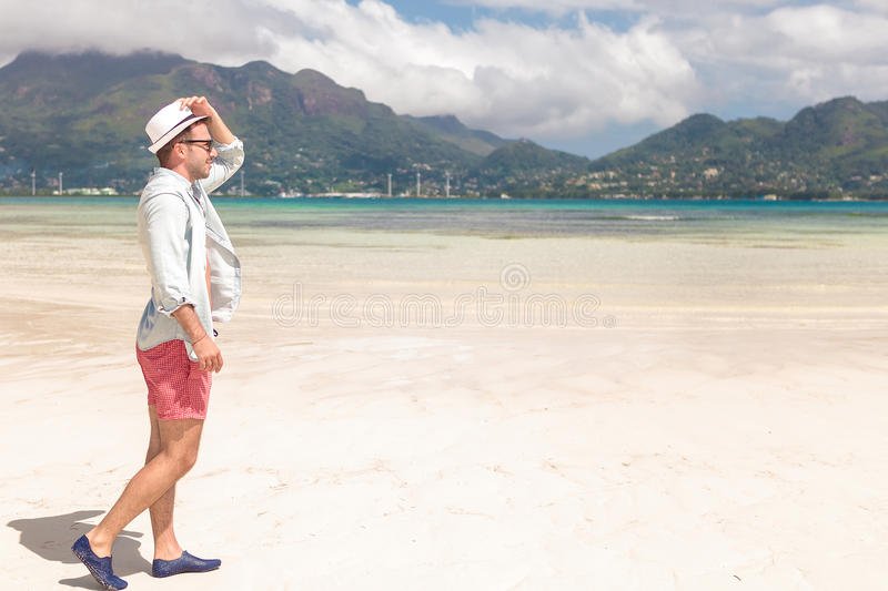 Side view of a young man walking on the beach royalty free stock image