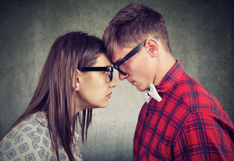 Side view of man and woman head to head looking with hatred at each other stock image