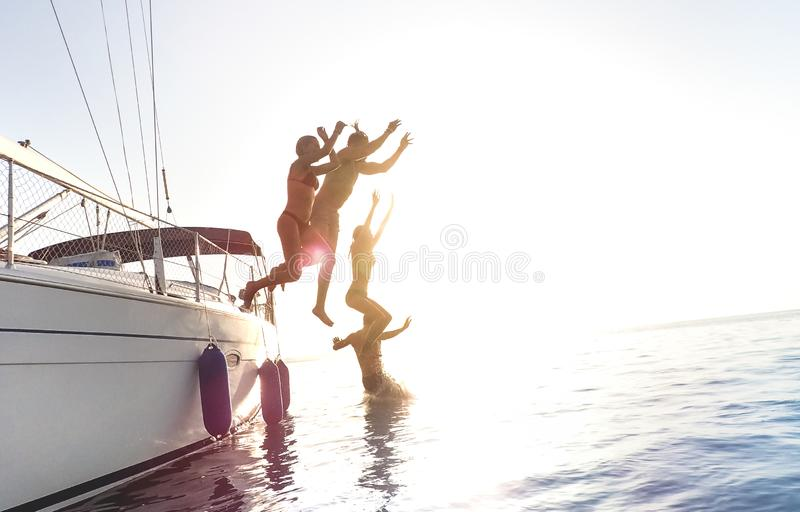 Side view of young millennial friends jumping from sailboat on sea ocean trip - Guys and girls having summer fun together. E view of young millennial friends stock photos