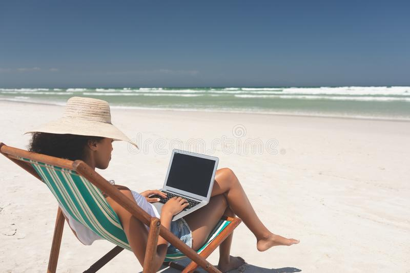Young woman holding laptop while sitting on sun lounger at beach stock image