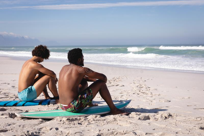Young men sitting on surfboard at beach in the sunshine stock image