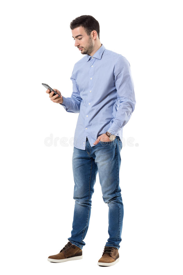 Side view of young smart casual business man reading message on cell phone stock images