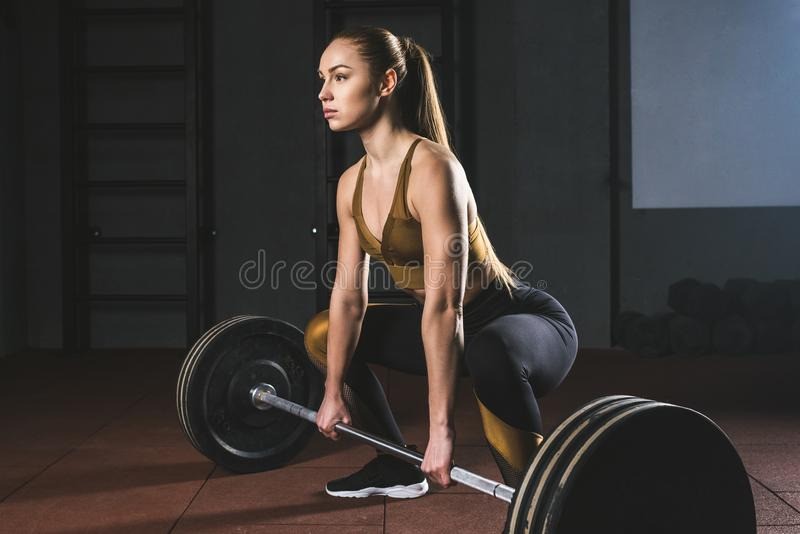 Side view of young sportswoman. Preparing to raise barbell in gym royalty free stock images