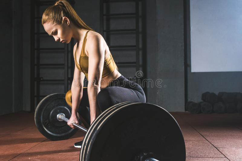 Side view of young sportswoman. Preparing to raise barbell in gym royalty free stock photo