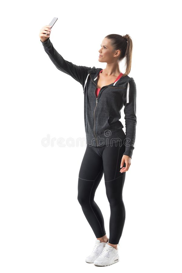 Side view of young sporty fitness woman taking selfie photo with mobile phone. Full body length portrait isolated on white background stock photography