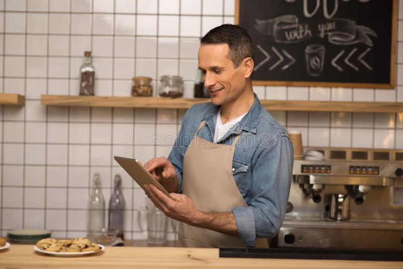 Waiter using digital tablet in cafe. Side view of young waiter using digital tablet in cafe royalty free stock photography