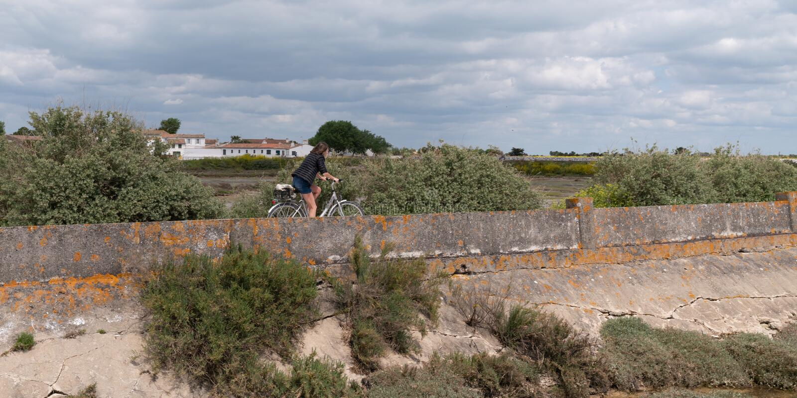 Side view young woman cycling at seaside dike on island Ile de Re in France stock image