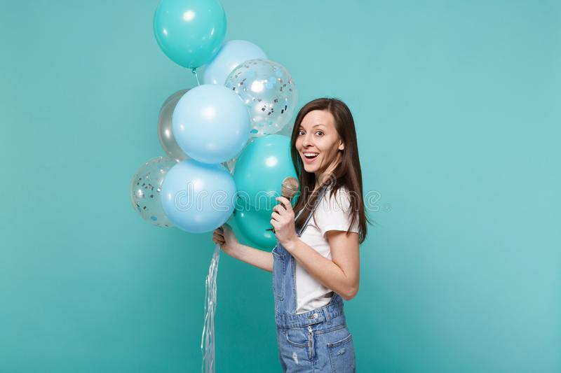 Side view of young woman in denim clothes sing song in microphone celebrating holding colorful air balloons isolated on. Blue turquoise wall background stock images