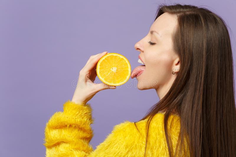 Side view of young woman in fur sweater hold licking half of fresh ripe orange fruit isolated on violet pastel. Background in studio. People vivid lifestyle stock photography