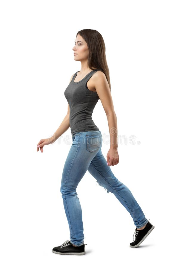Side view of young woman in gray sleeveless top and blue jeans, with long dark hazelnut hair, walking forward on white royalty free stock photography