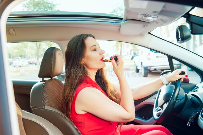 Side view young woman looking in rear view mirror and putting make up in car. Modern busy life. beautiful girl sitting in drivers royalty free stock photography