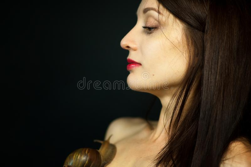Side View of Young Woman Receiving Snail Neck Massage in Studio on Black Background.  royalty free stock photography