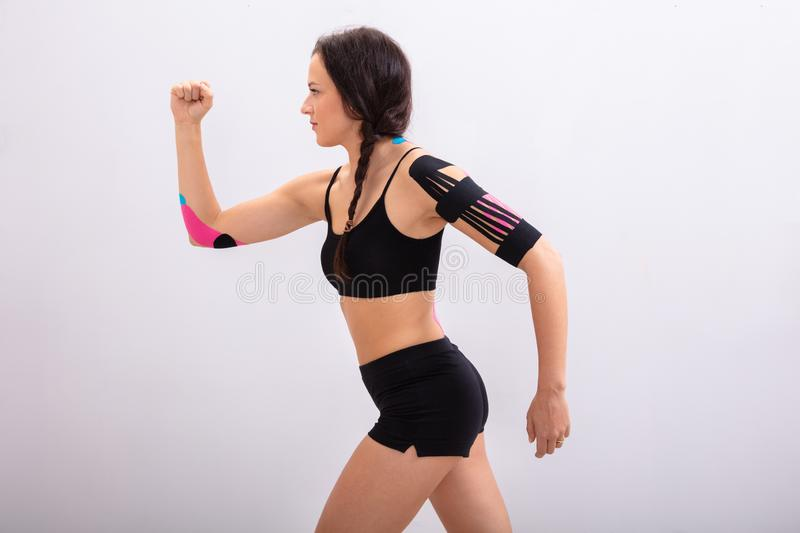Woman Running With Physio Tape On Her Body. Side View Of A Young Woman Running With Physio Tape On Her Body royalty free stock photography