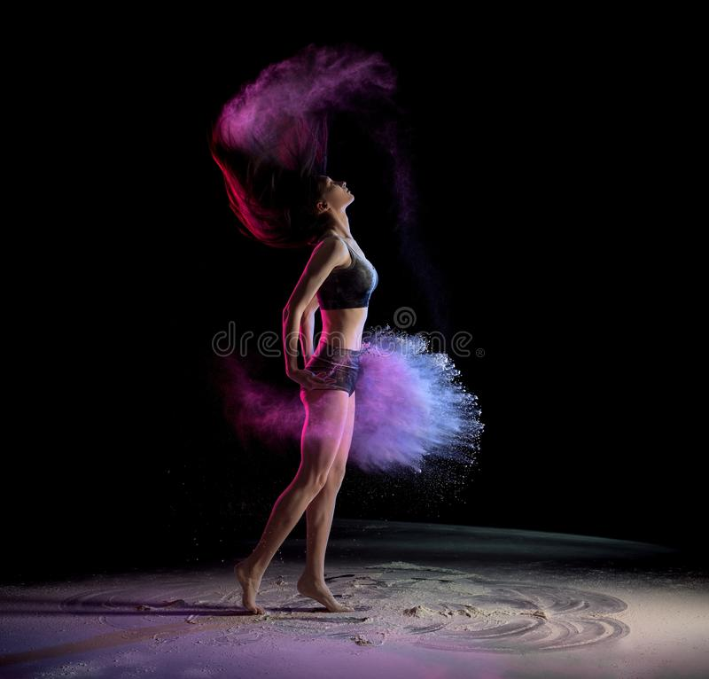 Young woman shaking hair and throwing chalk while dancing stock image