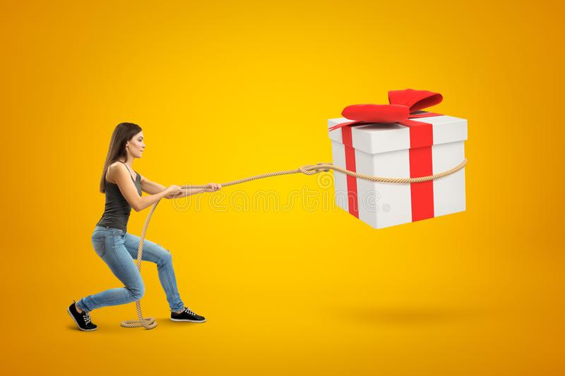 Side view of young woman standing with bent knees and pulling big gift box in air which she has lassoed, on yellow royalty free stock images