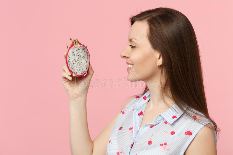 Side view of young woman in summer clothes holding half of fresh ripe pitahaya, dragon fruit isolated on pink pastel. Wall background. People vivid lifestyle stock photos
