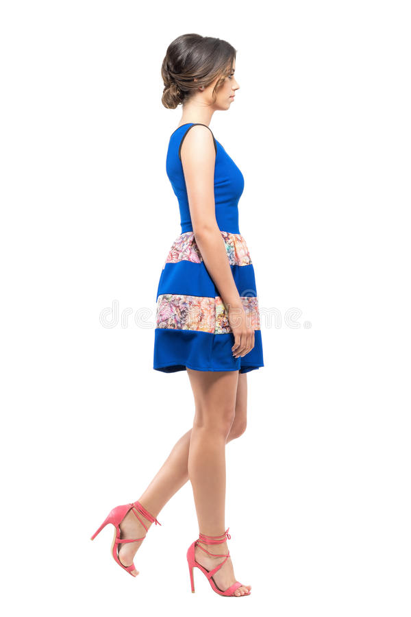 Side view of young woman in summer sleeveless blue short dress walking looking ahead. royalty free stock photos
