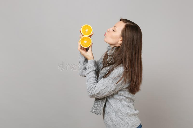 Side view of young woman in sweater, scarf blowing sending air kiss to oranges isolated on grey background. Healthy royalty free stock photography